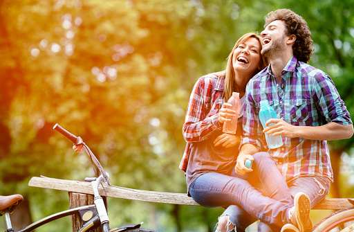 Young Cheerful couple having healthy lifestyles, riding bicycles outdoors in a nature. Having break, drinking water and having fun.