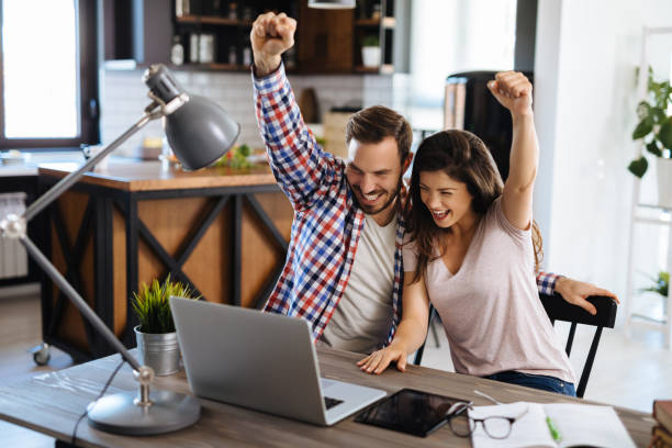 Young cheerful couple enjoying buying online stocks stock photo