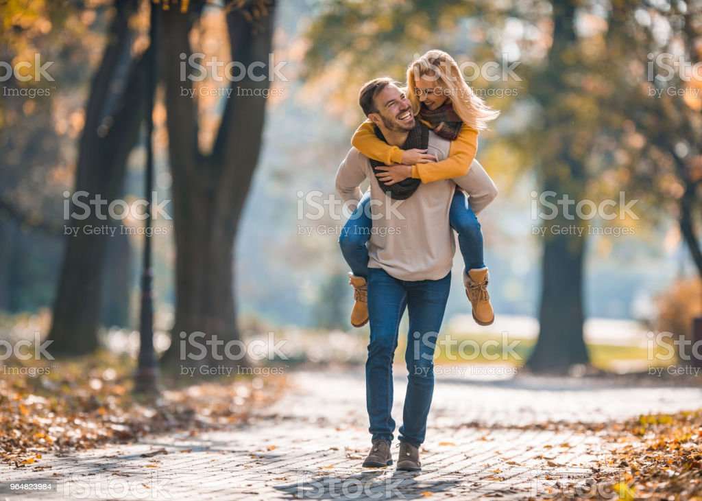 Young cheerful couple having fun while piggybacking in autumn day at the park. royalty-free stock photo