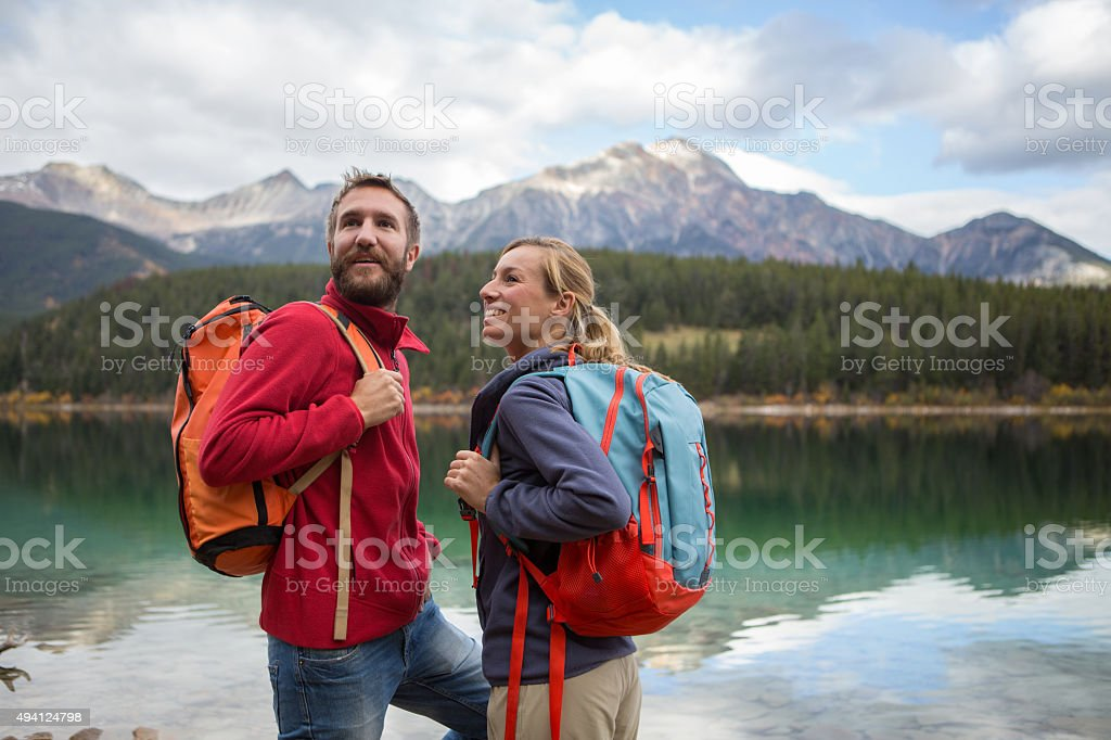 Young cheerful couple hiking by the lake in Autumn stock photo