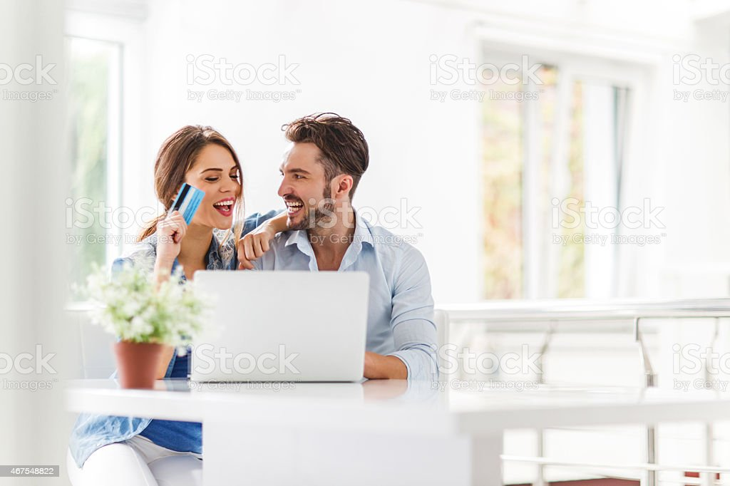 Young cheerful couple shopping online at home. stock photo