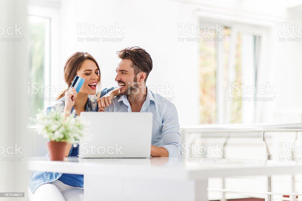 Junge fröhlich paar online-shopping zu Hause fühlen. – Foto