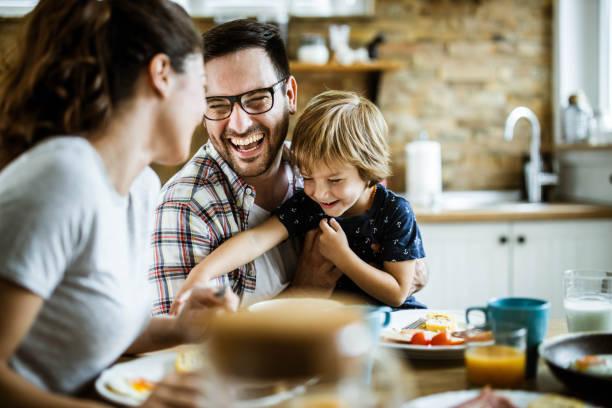 年輕開朗的家庭在餐桌上玩得很開心。 - 幸福 個照片及圖片檔