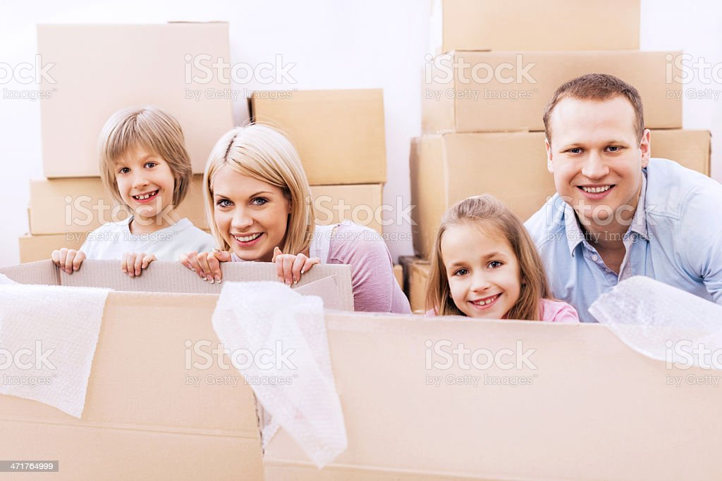 Young cheerful family in cardboard boxes. royalty-free stock photo