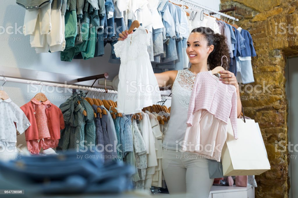 10622b190a Young Cheerful Female Customer Holding Baby Dress Stock Photo   More ...