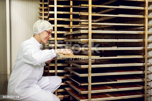 Young cheerful female worker in a sterile cloth examining freshly baked cookies on a cookie shelf in bakery storage room.