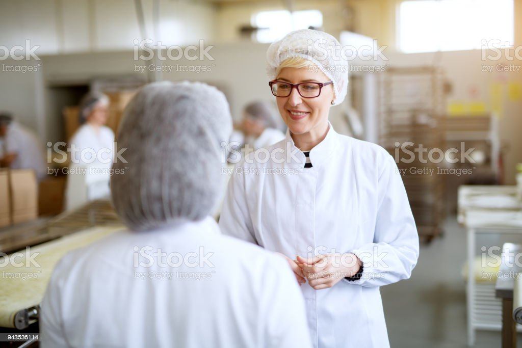 Young cheerful female workers are pleased with the production of food factory line while wearing sterile cloths. stock photo