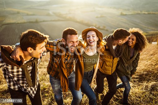 Group of cheerful friends having fun while walking embraced on the hill.