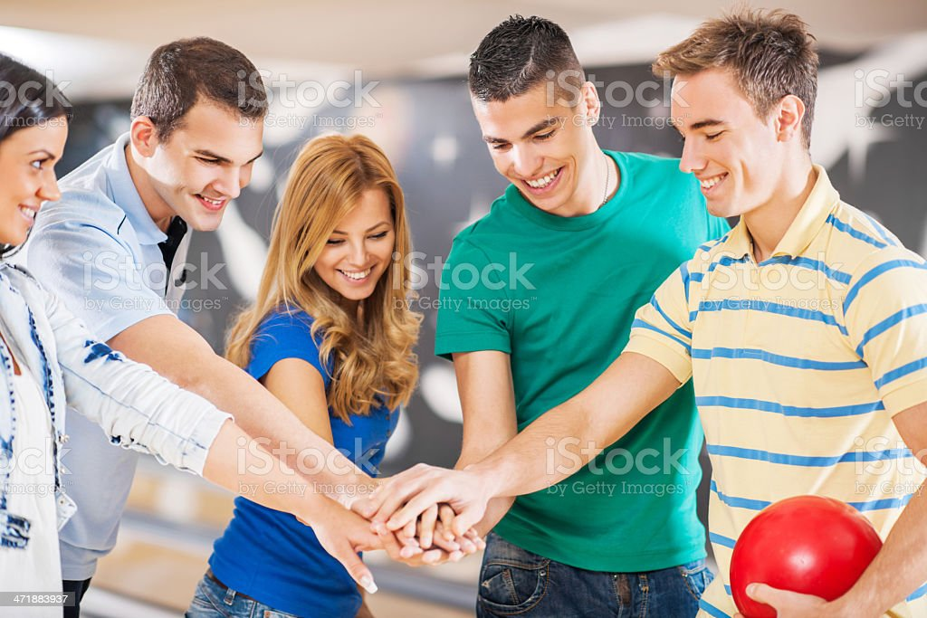 Young cheerful group of people bowling. stock photo