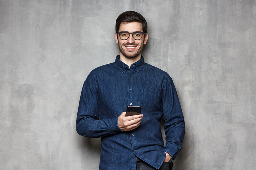 825083556 istock photo Young cheerful guy wearing denim shirt and trendy eyeglasses standing against gray textured wall with smart phone in one hand 1166255889