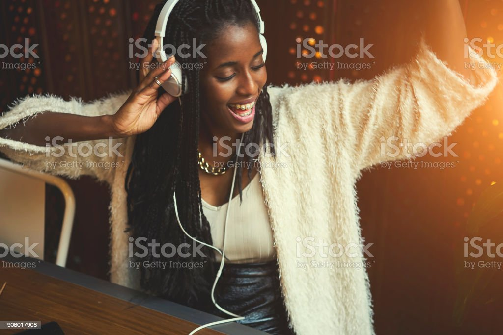 Young cheerful hipster female in casual wear listening music via big white modern headphones, afro american teen girl recreate while enjoying favorite songs from playlist sitting in cafe indoors stock photo