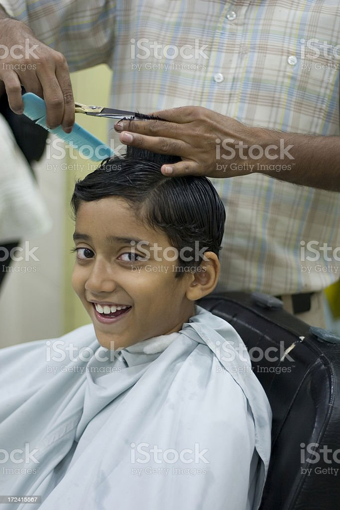 Young Cheerful Indian Boy Getting Hair Cut At Saloon Vertical Stock