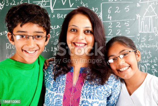 istock Young Cheerful Indian Teacher with her Students Kids 186810060