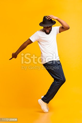 istock Young cheerful man dancing on tiptoes on yellow studio background 1172135938