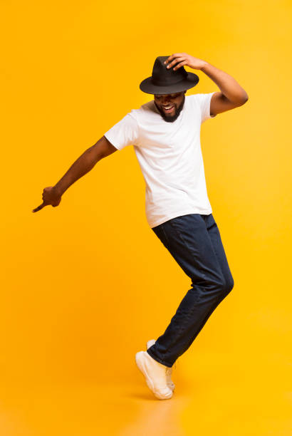 Young cheerful man dancing on tiptoes on yellow studio background Cheerful african man dancing on tiptoes, copy michael jackson style on yellow studio background dancing stock pictures, royalty-free photos & images