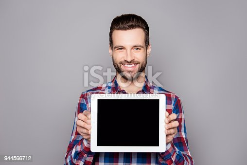 682621548istockphoto A young cheerful man in checkered shirt isolated on gray background demonstrating black screen of his tablet 944566712