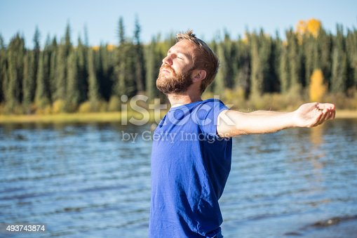 istock Young cheerful man relaxing by the lake arms outstretched 493743874