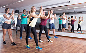 Young cheerful people dancing zumba elements in dancing class