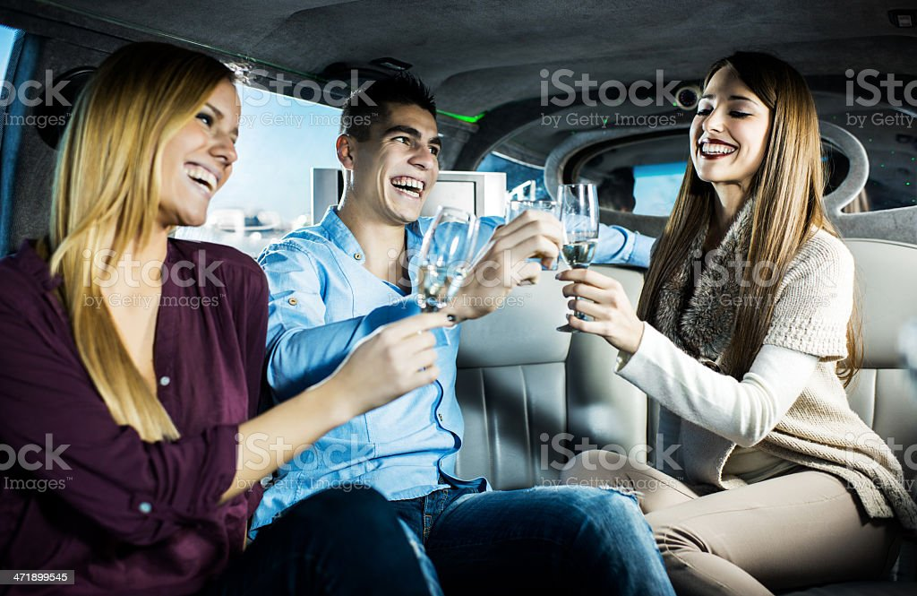 Young cheerful people in a limousine. royalty-free stock photo