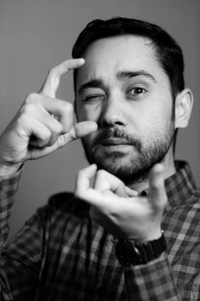 Junger fröhlicher Fotograf mit Bart, während er im Studio arbeitet – Foto