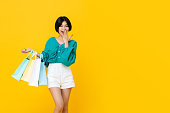 Young cheerful shopaholic Asian girl with lots of shopping bags on her arm isolated on yellow studio background with copy  space