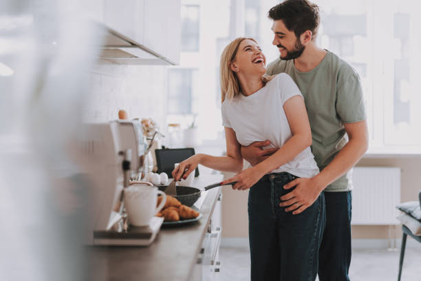 Young cheerful spouses enjoying morning time together Cooked with love. Cute laughing blonde frying something in skillet. Her bearded husband is hugging her from behind husband stock pictures, royalty-free photos & images