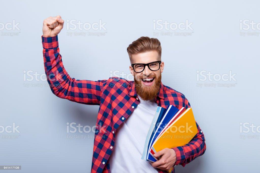 Junge fröhliche Studentin in Gläsern und im karierten Hemd mit Büchern in Händen feiert Ende der Prüfungen - Lizenzfrei Lernender Stock-Foto