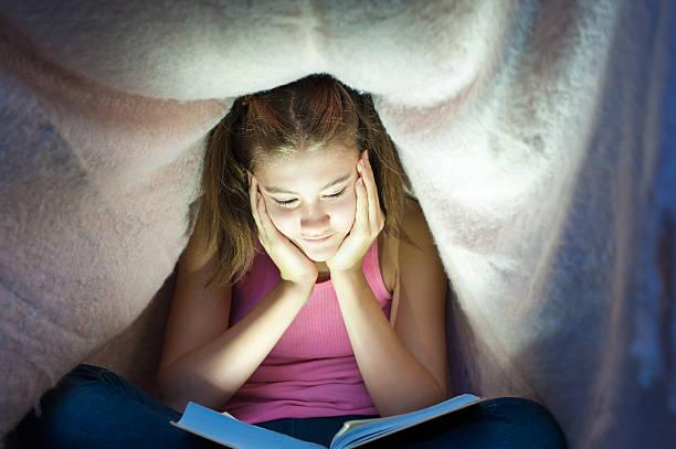 junge fröhliche teenager-mädchen versteckt unter der decke und liest buch - jagdthema schlafzimmer stock-fotos und bilder