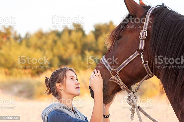 Young cheerful teenage girl stroking brown horses nose outdoors image picture id496664670?b=1&k=6&m=496664670&s=612x612&h=cgg w xcpgof39dydiatctynu0e60uzhud gkeckuxm=