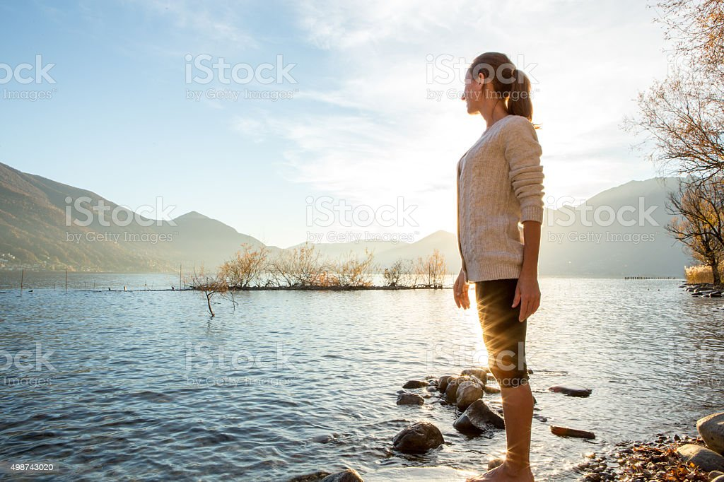 Young cheerful woman by the lake watching the sunset stock photo