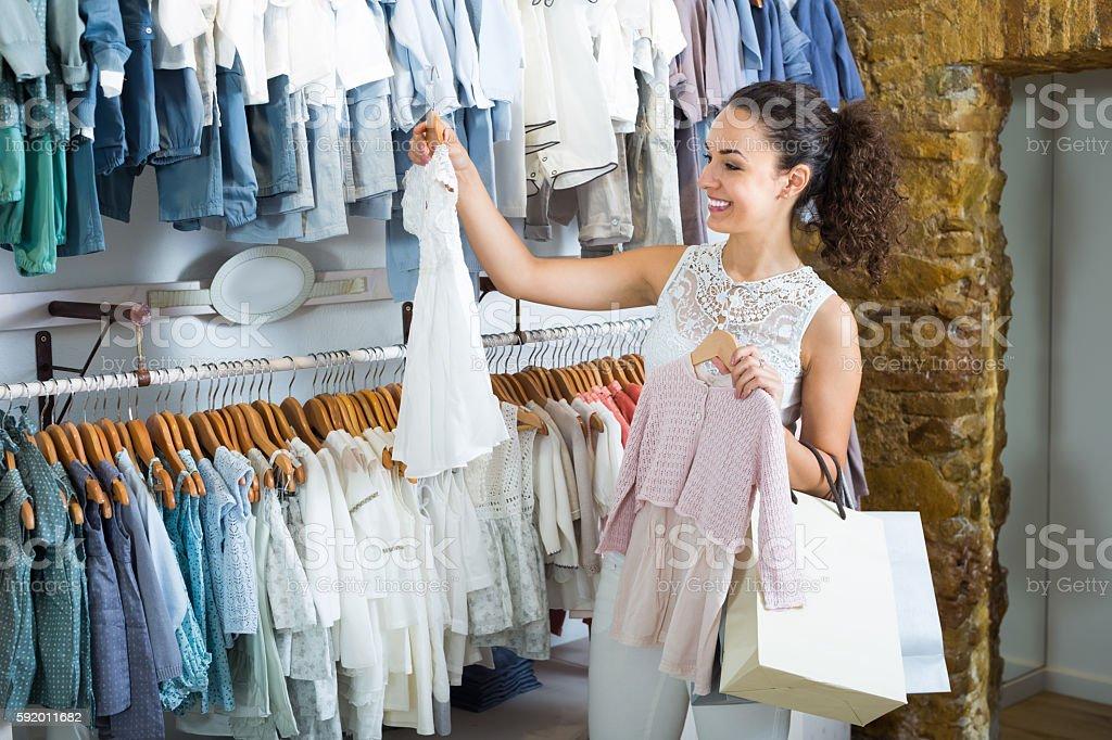 Young cheerful woman choosing baby dress - Photo