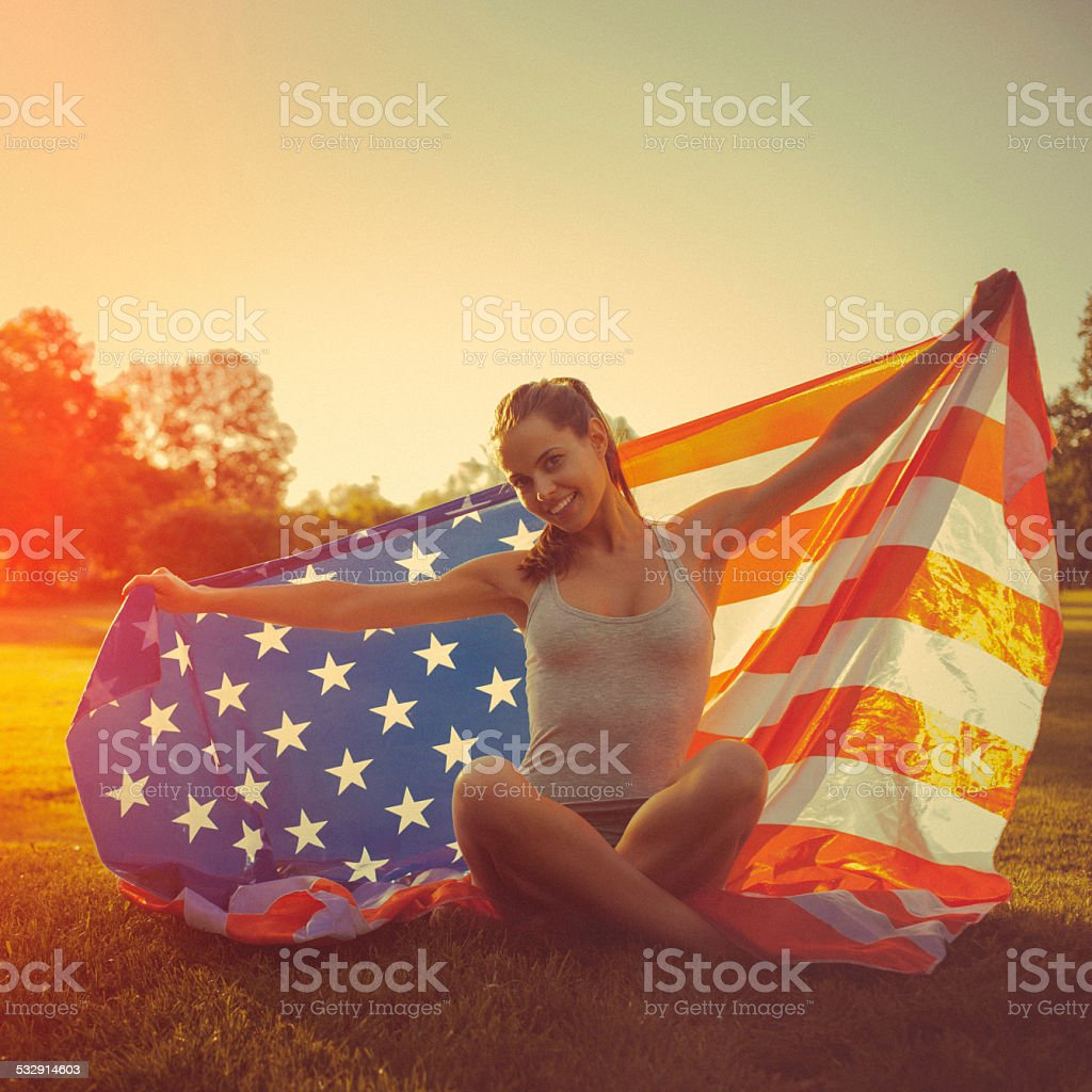 Young cheerful woman holding an american flag stock photo