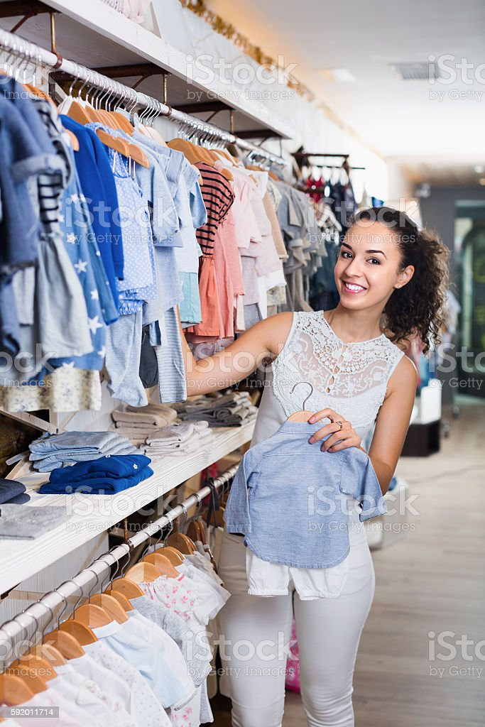 cae523445 Young Cheerful Woman Holding Blue Baby Clothes Stock Photo & More ...