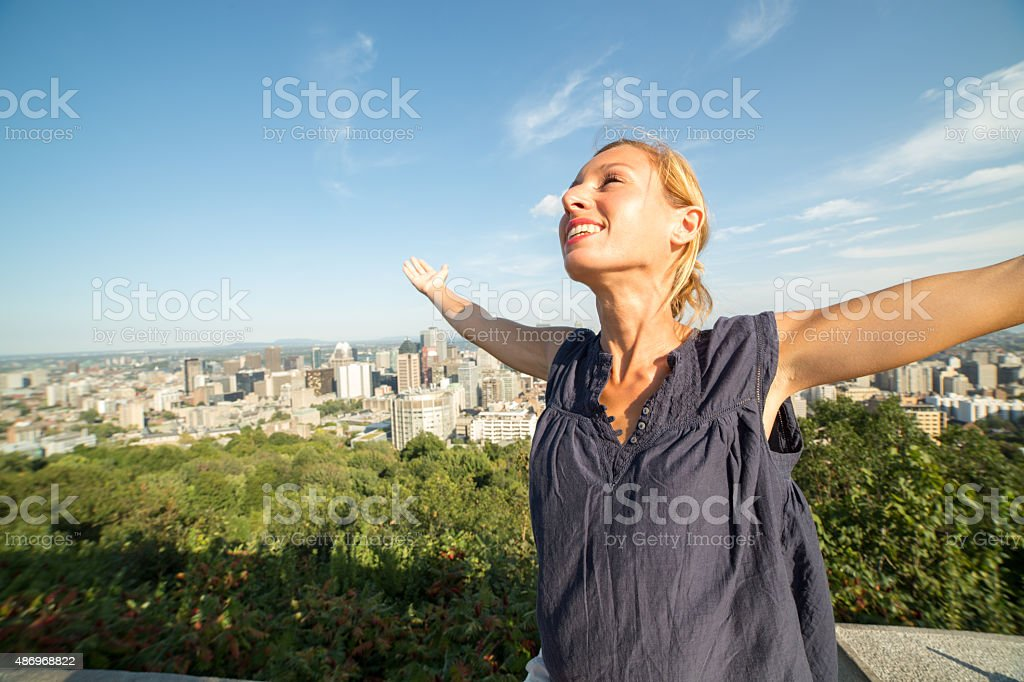 Young cheerful woman in Montreal-Canada arms outstretched for positive emotion stock photo