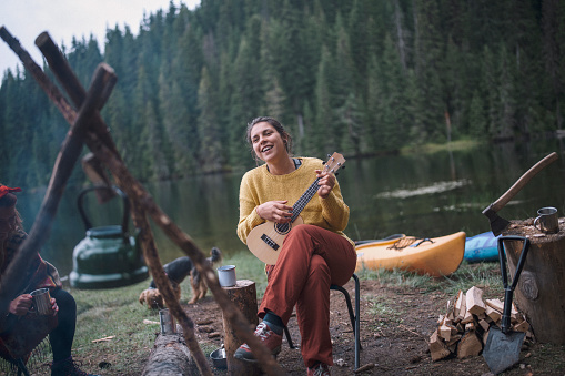 Young smiling female is having fun next to the camp fire while playing ukulele during her autumn camping vacation