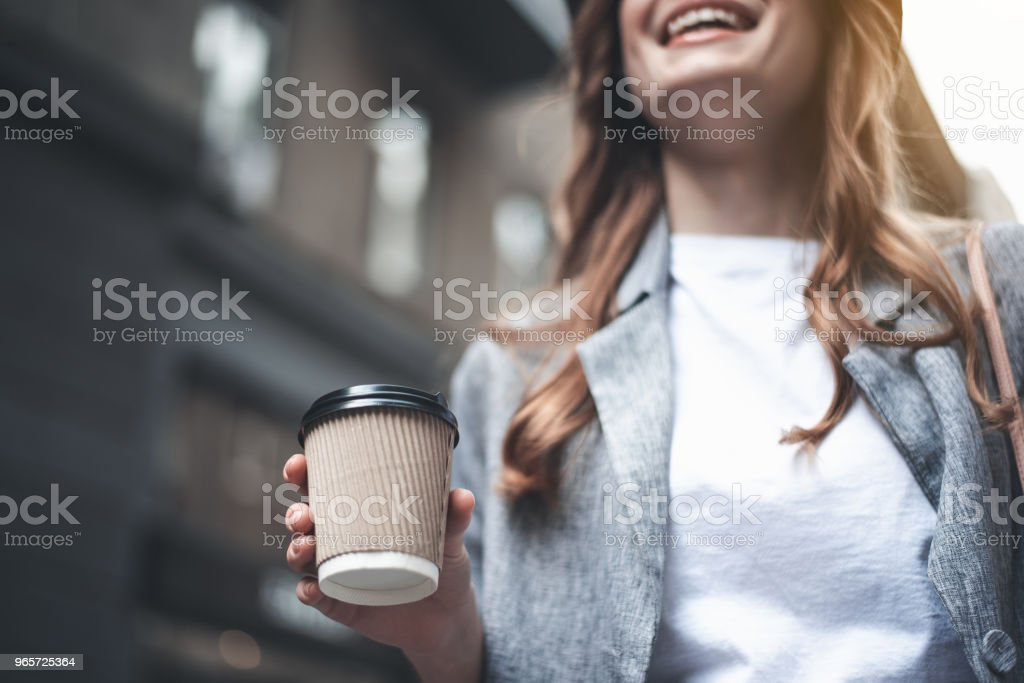 Young cheerful woman is holding cup of coffee - Royalty-free Adult Stock Photo