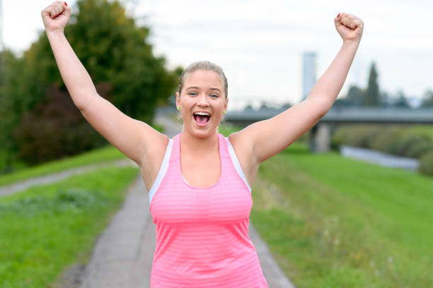young cheerful woman raising hands while running - carpet runner stock photos and pictures