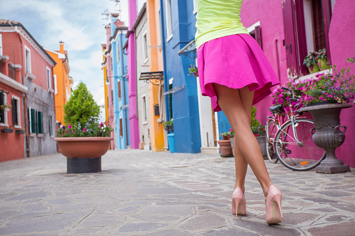 Young cheerful woman walking in streets of old town
