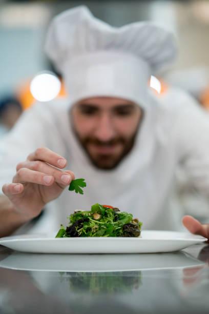 hinzufügen von details zu einem salat jungkoch bereitete er nur schauen glücklich - erdnusssalatdressings stock-fotos und bilder