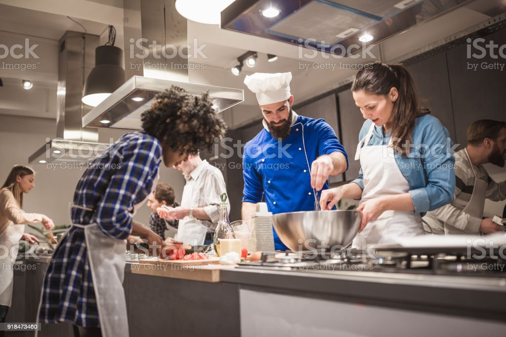 Young chef assisting a cooking class and explaining some tips and tricks stock photo