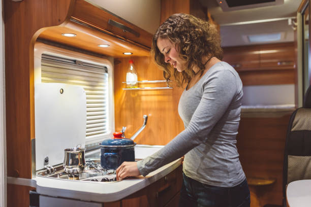 Young chef cooking in a caravan Young chef cooking in a caravan rv interior stock pictures, royalty-free photos & images