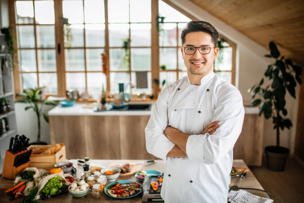 Young Chef in Uniform Posing in His Kitchen stock photo