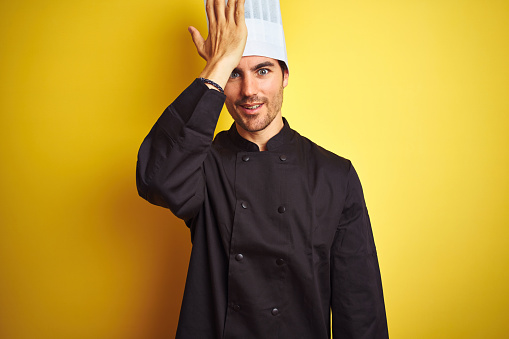 1046559700 istock photo Young chef man wearing uniform and hat standing over isolated yellow background surprised with hand on head for mistake, remember error. Forgot, bad memory concept. 1174439888