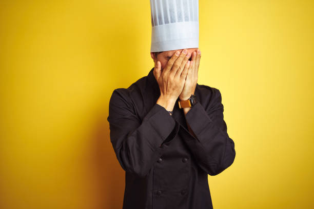 young chef man wearing uniform and hat standing over isolated yellow background with sad expression covering face with hands while crying. depression concept. - chef triste foto e immagini stock