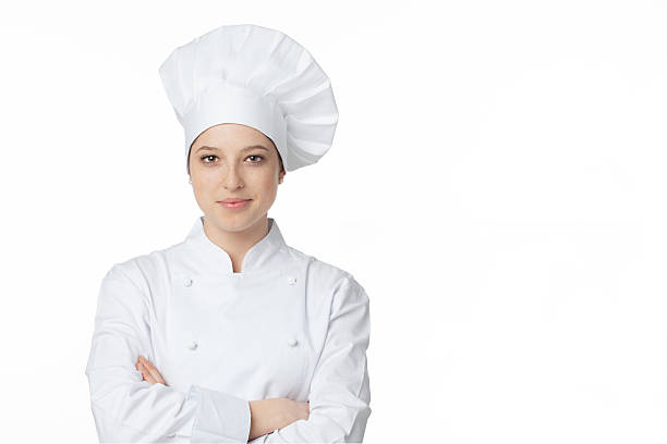Young chef A young, female chef in a traditional hat and coat. chef's whites stock pictures, royalty-free photos & images