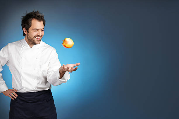Young chef playing with apple stock photo
