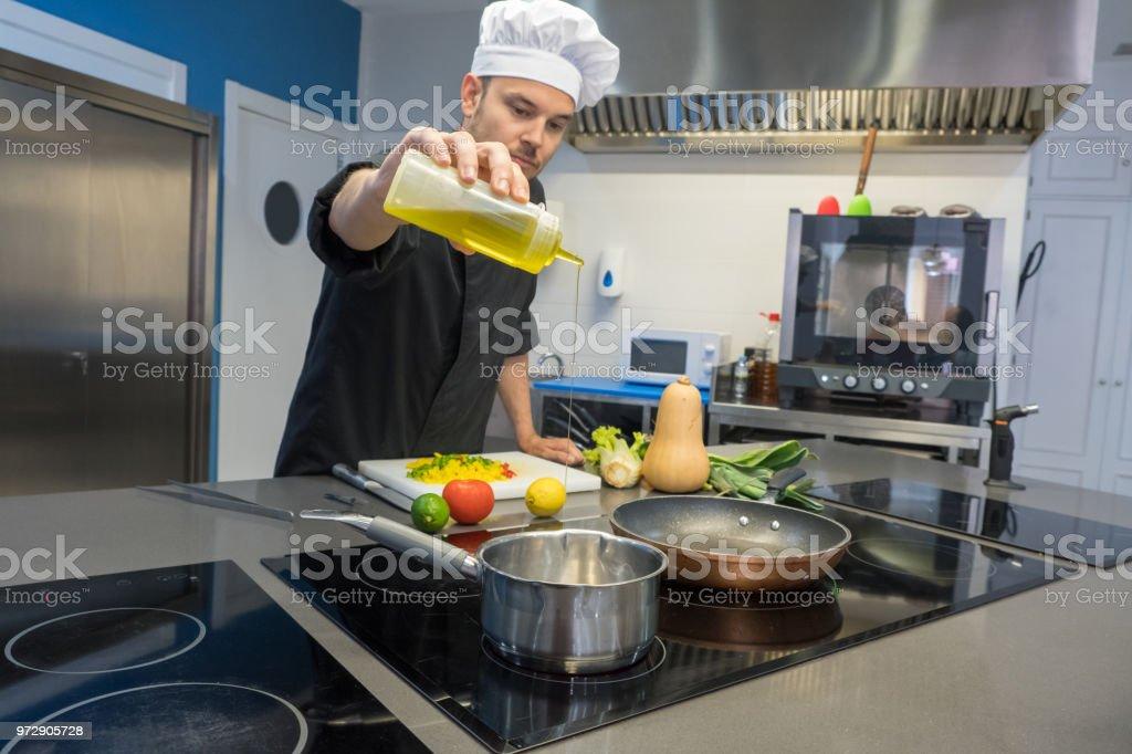 joven chef verter aceite de oliva en la olla en una cocina profesional - foto de stock