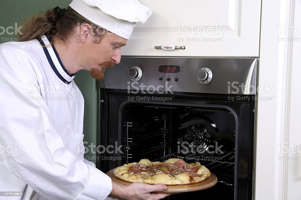Young chef prepared italian pizza in kitchen royalty-free stock photo