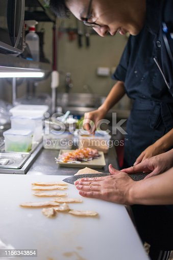 Young chef slicing chicken in kitchen