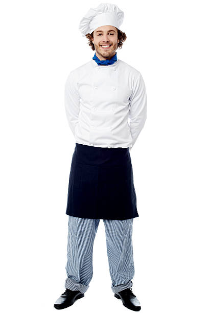 Young chef standing with hands behind stock photo